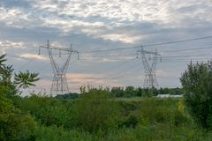 Twin Power Line Towers During Sunset. Twin power line towers in a large open green field on a cloudy day during sunset stock photography