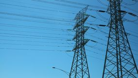 Twin power transmission towers on a sunny day. Two electrical power transmission towers under a clear blue sky, as well as power lines stock image