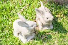 Twin rabbits of plaster decorated in green grass Royalty Free Stock Photography