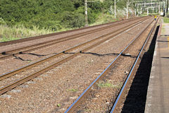 Twin Rail Tracks Leading Through Rural Railway Station Royalty Free Stock Photography