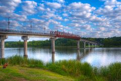 Twin Rivers Bridge Park. Early Morning Twin Rivers Pedestrian Bridge with Puffy White Clouds Over The Arkansas River Stock Photo