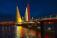Twin Sails lifting bridge and reflections, Poole Harbour in Dors. The Twin Sails Lifting Bridge was illuminated gold in support of childhood cancer. The red Royalty Free Stock Photography