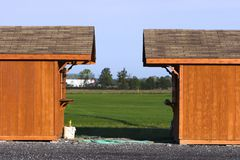 Twin sheds. Two wooden sheds facing each other stock images