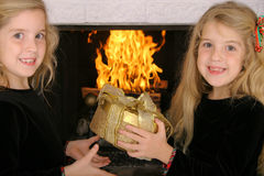 Twin sister gift exchange by fireplace Royalty Free Stock Image