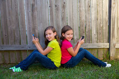 Twin sister girls playing smartphone sitting on backyard lawn Stock Photos