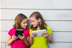 Twin sister girls playing with tablet pc happy on white wall Royalty Free Stock Photography