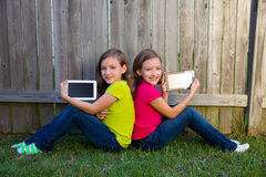 Twin sister girls playing tablet pc sitting on backyard lawn Royalty Free Stock Photo