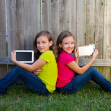 Twin sister girls playing tablet pc sitting on backyard lawn Stock Image