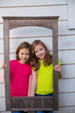 Twin sister girls posing with aged wooden border frame. On white wall stock photos
