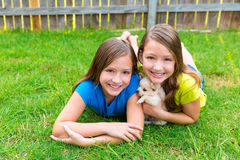 Twin sister kid girls and puppy dog lying in lawn stock photography