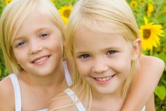 Twin sisters. Portrait of cute girl embracing her twin sister and both looking at camera with smiles royalty free stock image