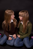 Twin sisters. Twin girls, sisters, look at each other and smile stock photo