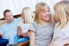 Twin sisters. Affectionate twin sisters having fun in the foreground, their parents sitting behind Stock Photo
