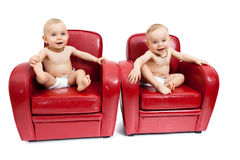 Twin sisters on armchairs. Twin sisters sitting on  red armchairs Royalty Free Stock Photography