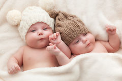 Twin sisters babies lying together wearing funny woolen bobble hats. Stock Image