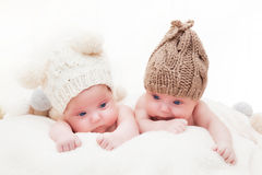 Twin sisters babies lying together wearing funny woolen bobble hats. Royalty Free Stock Photography