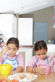 Twin Sisters Beating Eggs in Kitchen Royalty Free Stock Photography