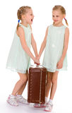 Twin sisters with a big old suitcase. Stock Images