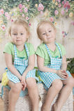 Twin sisters in blue aprons,. They sit Royalty Free Stock Image