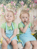 Twin sisters in blue aprons,. They sit Royalty Free Stock Images