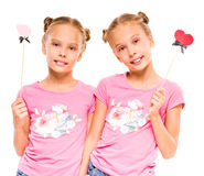 Twin sisters. Cheerful twins girls are ready to the party with paper handmade Royalty Free Stock Photo