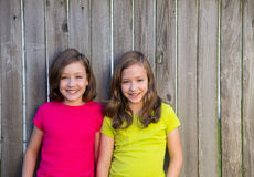 Twin sisters with different hairstyle posing on wood fence Royalty Free Stock Photos