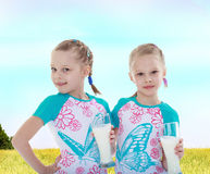 Twin sisters drink milk from a big cup. Royalty Free Stock Photos