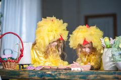 Twin sisters at Easter eat ginger cookies, painted eggs, laugh. Girls in the kitchen in costumes chicken royalty free stock image