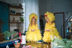 Twin sisters at Easter eat ginger cookies, painted eggs, laugh. Girls in the kitchen in costumes chicken royalty free stock photo
