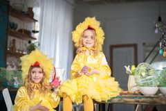 Twin sisters at Easter eat ginger cookies, painted eggs, laugh. Girls in the kitchen in costumes chicken stock images