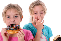 Twin sisters eating a donut. Shot of twin sisters eating a donut isolated on white Royalty Free Stock Photography