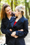 Twin Sisters - Fraternal Twins. Beautiful fraternal twin sisters glancing at each other while hugging and loving royalty free stock images