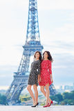 Twin sisters in front of the Eiffel tower in Paris, France Stock Image