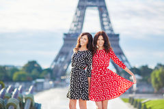 Twin sisters in front of the Eiffel tower in Paris, France Stock Photo