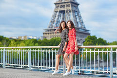Twin sisters in front of the Eiffel tower in Paris, France. Beautiful twin sisters in red and black polka dot dresses in front of the Eiffel tower in Paris Royalty Free Stock Photos