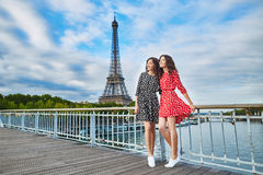 Twin sisters in front of the Eiffel tower in Paris, France Stock Photography