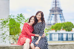 Twin sisters in front of the Eiffel tower in Paris, France Stock Photos
