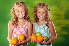 Twin sisters holding fruits. Beautiful twin girls holding fruits Royalty Free Stock Image