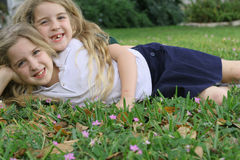 Twin sisters laying in the grass. Shot of twin sisters laying in the grass stock photography