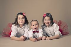 Twin sisters with little brother. Portrait of twin sisters with little brother at the studio Stock Images