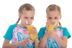 Twin sisters love to drink orange juice. Royalty Free Stock Images