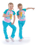 Twin sisters love to drink orange juice. Stock Photography