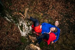 Twin sisters lying in autumn forest Royalty Free Stock Images