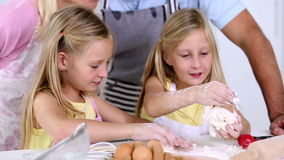 Twin sisters making pastry with their parents. At home in the kitchen stock video footage
