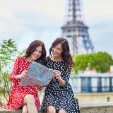 Twin sisters with map near the Eiffel tower in Paris. Tourists enjoying their vacation in France. Romantic date or traveling couple concept Royalty Free Stock Images