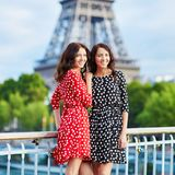 Twin sisters near the Eiffel tower in Paris. Tourists enjoying their vacation in France. Romantic date or traveling couple concept Stock Photography