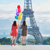 Twin sisters near the Eiffel tower in Paris. Twin sisters with bunch of colorful balloons near the Eiffel tower in Paris. Tourists enjoying their vacation in Royalty Free Stock Image