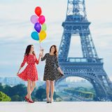 Twin sisters near the Eiffel tower in Paris. Twin sisters with bunch of colorful balloons near the Eiffel tower in Paris. Tourists enjoying their vacation in Stock Images
