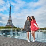 Twin sisters near the Eiffel tower in Paris. Tourists enjoying their vacation in France. Romantic date or traveling couple concept Stock Image
