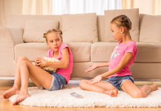Twin sisters. One of sisters hides a bucket of popcorn while watching tv with her twin sister Stock Images